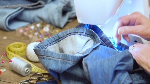 Sewing denim jeans with sewing machine. Repair jeans by sewing machine Live Action