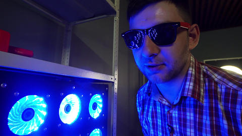 Funny bearded guy with sunglasses is standing next to blue illuminated coolers Footage