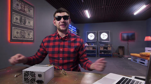 Cool looking man gives five to camera having box of power supply on desk Footage