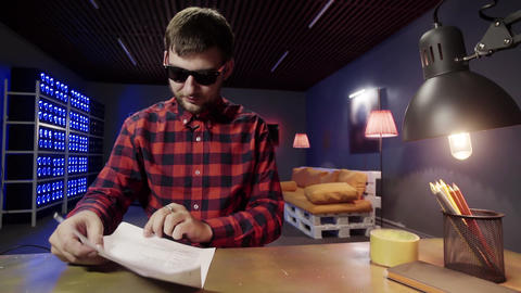 Bright cute guy with sunglasses puts sheet of paper on desk and reads it on desk Footage