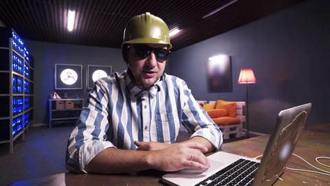 Young bearded male put on sunglasses and green safety construction helmet Live Action
