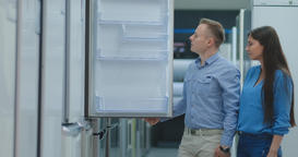 Young couple man and woman choose new fridge Footage