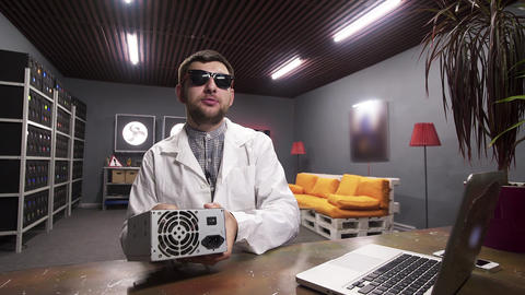 Cute male wearing lab coat speaks at camera holding box of power supply Archivo