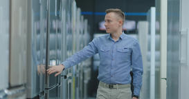 The man open the door of the refrigerator in the appliances store and compare Footage