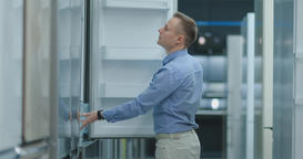 A young man in a blue shirt to open the door of the refrigerator in the Footage