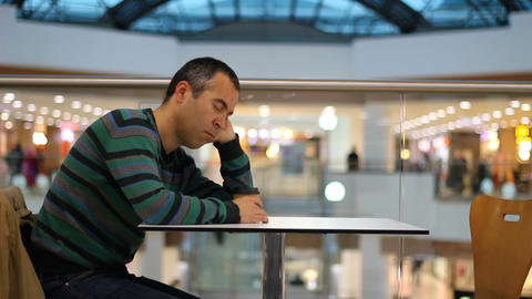 Tired man sleeping in shopping mall and cafe Live Action