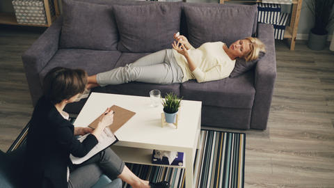 High angle view of stressed woman talking with therapist lying on sofa in office Archivo