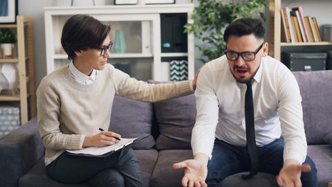 Helpful therapist comforting angry businessman during consultation in office Footage