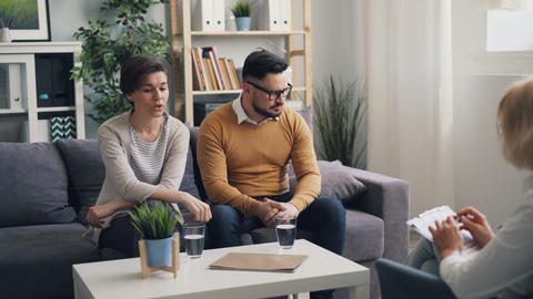 Unhappy couple fighting in psychologist's office talking to specialist in office Live Action