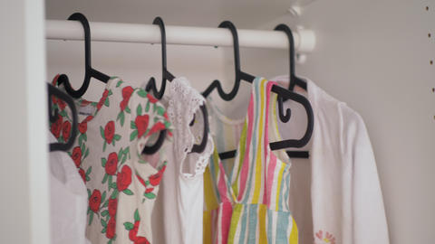 A close up of a baby girl clothes hanging in a wardrobe Footage