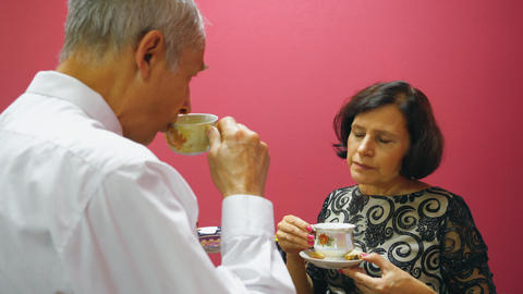 Senior couple drinking tea with cookie and talking. Elderly people lifestyle Footage