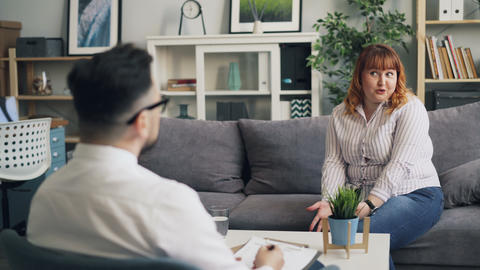 Emotional lady opening up to psychologist in modern office speaking gesturing Footage