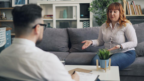 Upset overweight woman is opening up to caring male therapist in office Live Action