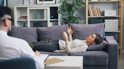 Young woman speaking with psychologist lying on sofa in office talking gesturing Footage