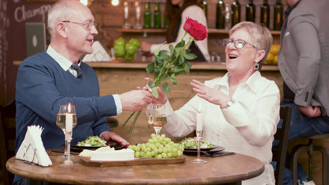 Old man offers flowers to his date on a romantic dinner Footage