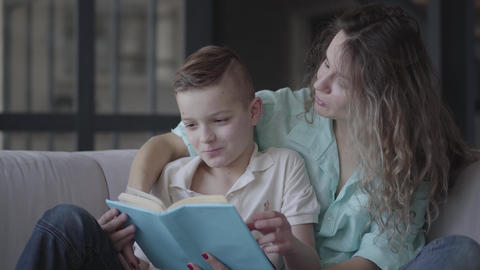 Portrait of a beautiful young mother reading a book to her beautiful son sitting Footage