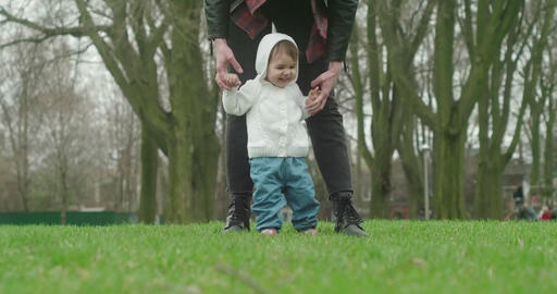Little baby girl learns to walk with the help of her mother Footage