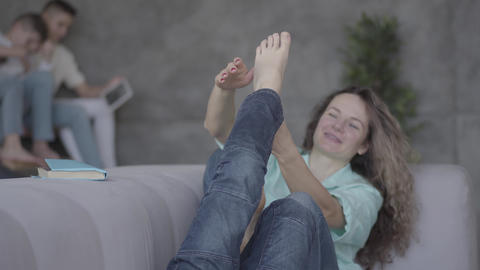 Pretty young mother sitting on the sofa with her lying son. The boy playing with Footage