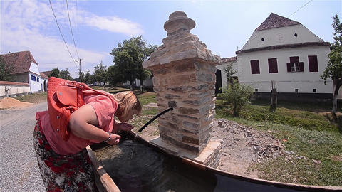 Woman drink water from a spring arranged on the main street of the small village Footage
