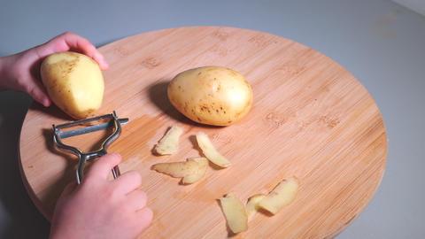 Hands of little girl peeling potatoes with peeler on wooden desk ビデオ
