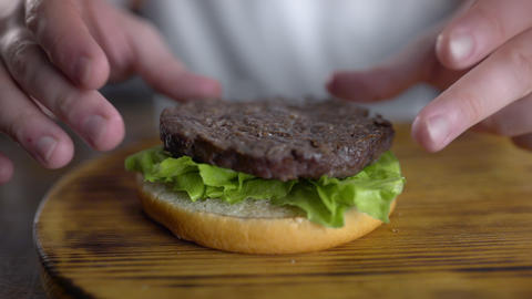Chef cooks burger and puts cutlet to the leafs of fresh green salad, fast food Footage