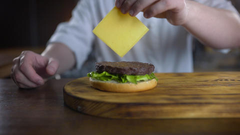 Chef adds sliced cheddar cheese to the burger and puts it over cutlet, cooking ライブ動画