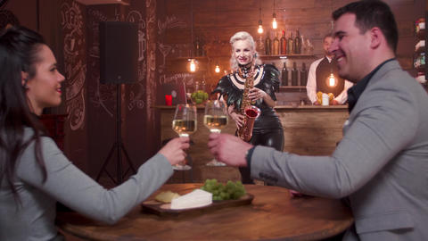 Woman performing a song on a saxophone while audience clink glasses and drink GIF
