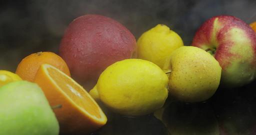 Tropical lemon, orange, apple in cold ice clouds of fog smoke on dark background Footage