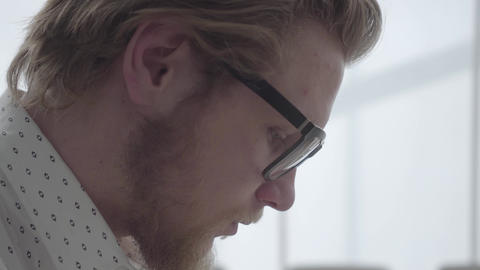 Face of blond thoughtful man in glasses sitting in a light comfortable office Footage
