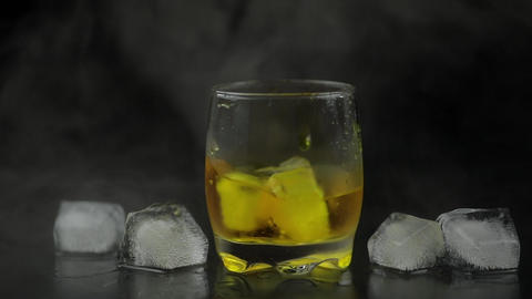 Whiskey with ice. Adding ice cubes on black background. Glass of rum alcohol Footage