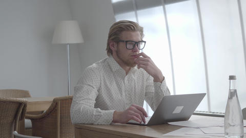 Blond thoughtful man in glasses sitting at the table in a light comfortable Footage