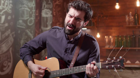 Man plays a rythm on an acoustic guitar at a solo concert GIF