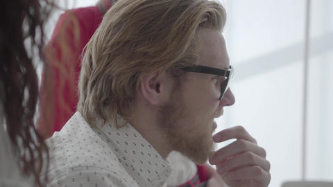 Close up portrait successful blond man in glasses sitting in a light comfortable Footage