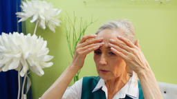 Elderly woman is making anti-aging facial massage against wrinkles ビデオ