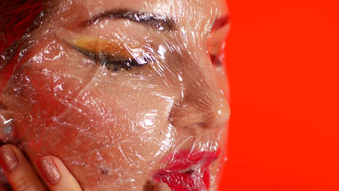 plastic film on the face. Beautiful girl. environmental pollution concept. We Live Action