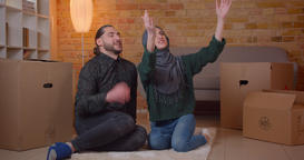 Closeup shoot of young cheerful muslim couple sitting on the floor next to the Footage