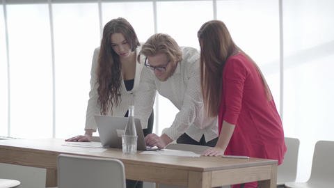 Handsome blond man in glasses bent over netbook in a light comfortable office Footage