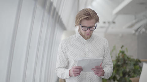 Blond thoughtful man in glasses standing in a light comfortable office reading Footage