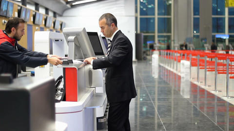 Passenger business man at the airport check in desk. Staff handing ticket to passenger Footage