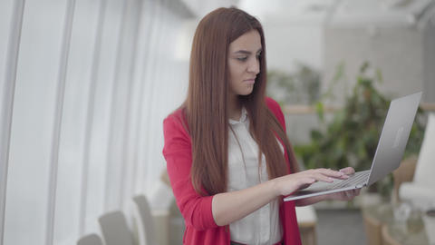 Young woman in red suit typing on her gadget in modern light office. The girl Live Action