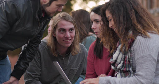 Diverse group of four college students looking at a laptop computer outside on a university campus Footage