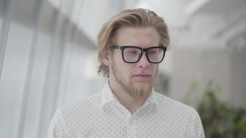 Portrait successful blond man in glasses standing in a light comfortable office Footage