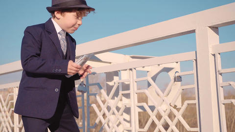 Little boy looking like a businessman in suit is overspend money, throws money Live Action