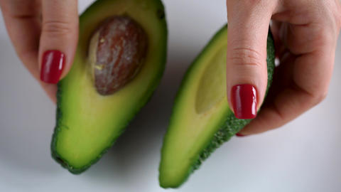 Woman opens avocado. The concept of modern healthy eating Footage