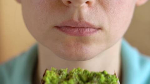 Woman eating vegan avocado sandwich closeup Footage