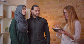 Closeup shoot of young happy muslim couple talking to realter holding a tablet ビデオ