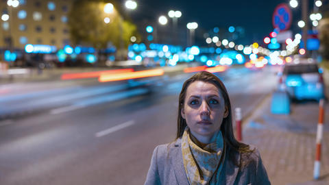 Timelapse of woman standing still on crowded evening street while a blur of fast Footage