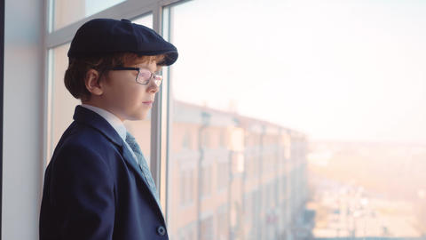 Young boy in business suit, tie and cap looks out from window in business office Live Action