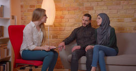 Closeup shoot of young happy muslim couple discussing with a realter a new Footage