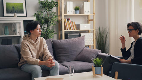 Friendly psychologist young woman counseling unhappy teenager in office Footage